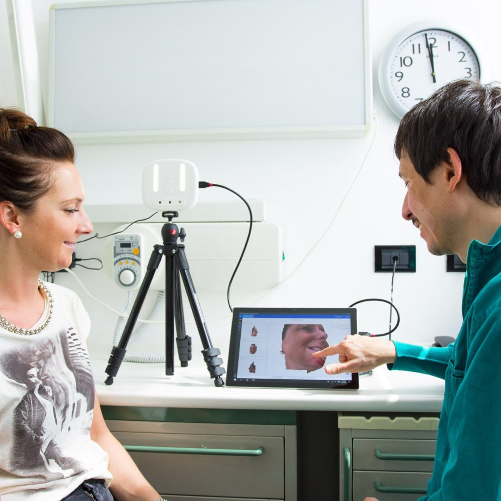 ObiScanner connected to a tablet. The dentist is showing his patient the face scan just acquired, for a better communication